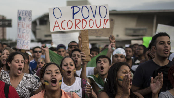 "Residents of the upper middle class neighborhood Barra da Tijuca shout slogans as they hold a banner that reads in Portuguese; ""The people woke up,"" during an anti-goverment protest in Rio de Janeiro, Brazil, Friday, June 21, 2013. Demonstrations began as an outcry against a 10-cent hike in bus and subway fares in Brazil's largest cities, but have continued even after announcements that the increases would be rescinded. Protesters have expressed frustration with corruption and what they say are high taxes and poor public services. They've demanded everything from education reforms to free bus fares while denouncing the billions of public dollars spent on stadiums before the World Cup and the Olympics. (AP Photo/Felipe Dana)"