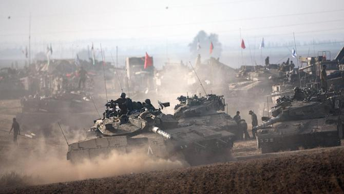 Israeli soldiers on Merkava tanks in an army deployment area near Israel's border with the Gaza Strip on July 12, 2014