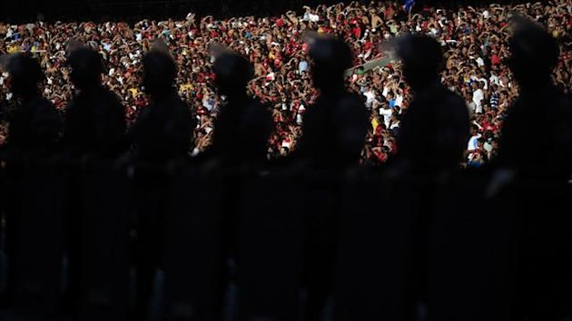 Fans of Flamengo cheer as riot police stand in line during their Brazilian Serie A Championship match against Fluminense at Joao Havelange Olympic Stadium in Rio (Reuters)