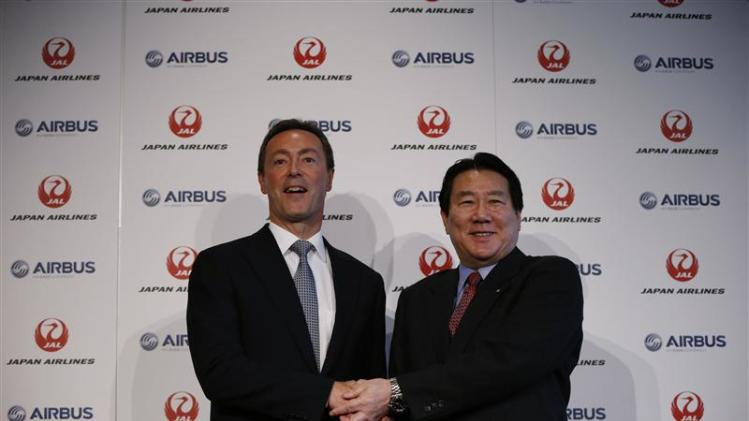 Japan Airlines President Ueki shakes hands with Airbus Chief Executive Bregier during their joint news conference in Tokyo