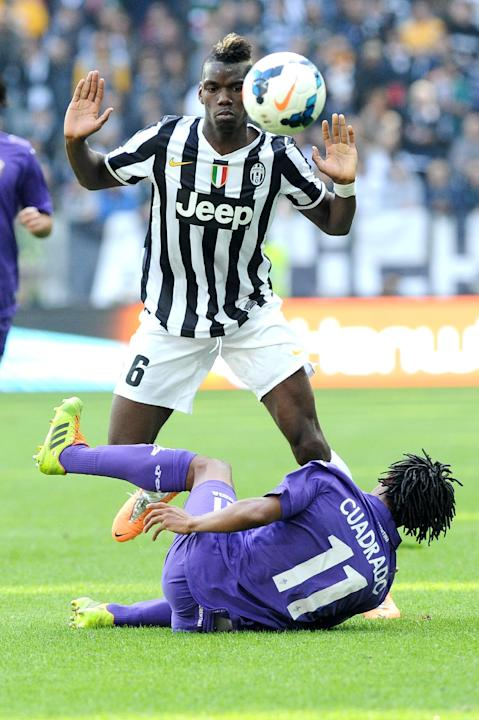 Juventus midfielder Paul Pogba, of France, standing, challenges for the ball with Fiorentina Colombian midfielder Juan Cuadrado, during a Serie A soccer match between Juventus and Fiorentina at the Ju