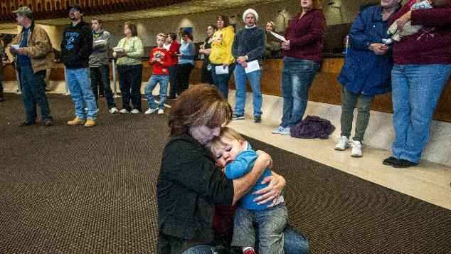 "Carla Coulter, 46, of Clio, holds her 1-year-old grandson Connor Hergert closely as she gives him a kiss on the forehead while listening to the FirstMerit Bank Mixed Chorus sing ""Silent Night"" along with about 100 spectators during the 76th Annual Holiday Sing on Tuesday, Dec. 24, 2013 at FirstMerit Bank in downtown Flint, Mich. ""We don't have power. We're warming up, and I just feel so very blessed to have my family,"" Coulter said. ""I don't need anything else."" (AP Photo/The Flint Journal, Jake May) LOCAL TV OUT; LOCAL INTERNET OUT"