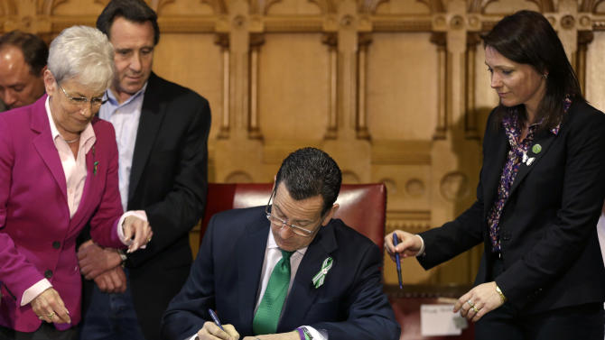 Connecticut Gov. Dannel P. Malloy, center, signs legislation at the Capitol in Hartford, Conn., Thursday, April 4, 2013, that includes new restrictions on weapons and large capacity ammunition magazines, a response to last year's deadly school shooting in Newtown. Neil Heslin, behind left, father of Sandy Hook shooting victim Jesse Lewis, Nicole Hockley, right, mother of Sandy Hook School shooting victim Dylan, and Conn. Lt. Gov. Nancy Wyman, left, look on. The legislation adds more than 100 firearms to the state's assault weapons ban, sets eligibility rules for buying ammunition, and creates what officials have called the nation's first dangerous weapon offender registry. (AP Photo/Steven Senne)