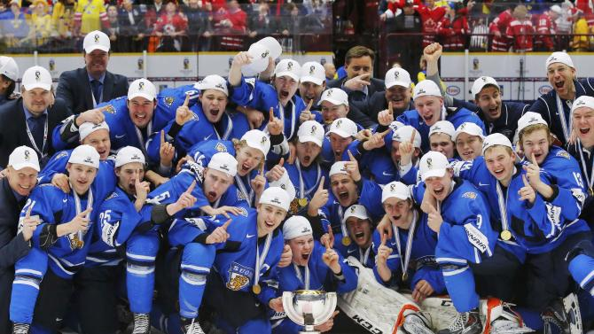 Finland players celebrate with the trophy after they defeated Sweden in overtime of their IIHF World Junior Championship gold medal ice hockey game in Malmo