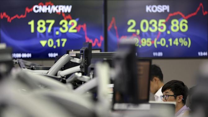 A currency trader works near the screen showing the Korea Composite Stock Price Index (KOSPI), right, at the foreign exchange dealing room of the Korea Exchange Bank headquarters in Seoul, South Korea, Tuesday, July 28, 2015. Shanghai stocks were volatile Tuesday after falling the most in eight years the day before while other Asian markets also flitted between gains and losses. (AP Photo/Lee Jin-man)