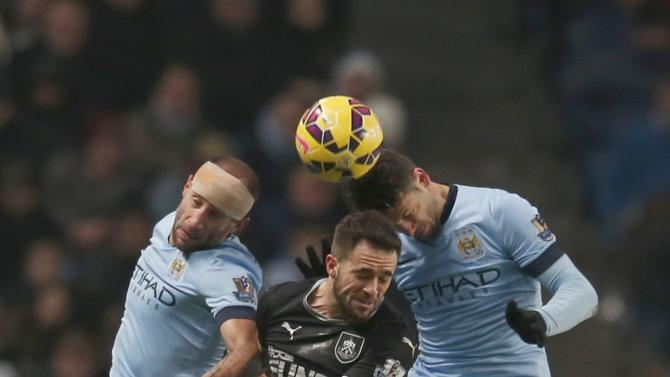 Burnley's Danny Ings is challenged by Manchester City's Pablo Zabaleta and Martin Demichelis during their English Premier League soccer match at the Etihad Stadium in Manchester