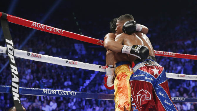 Yuriorkis Gamboa, from Miami, Fla., right, and Michael Farenas, from the Philippines, fall into a clinch against the ropes during their WBA interim super featherweight title fight Saturday, Dec. 8, 2012, in Las Vegas. (AP Photo/Eric Jamison)