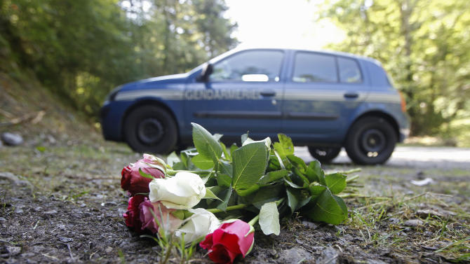 FILE - In this Sept. 8, 2012 file photo flowers are seen at the crime scene where four people have been shot to death in a British-registered car, in a forest in the Alps, near Chevaline, French Alps. The young sisters who survived the mysterious shootings in the French Alps are the only known witnesses to the crime, and experts say 4-year-old Zeena and 7-year-old Zaina could provide crucial help to the investigation into a killing that remains a mystery several days later, if handled carefully. (AP Photo/Laurent Cipriani, File)