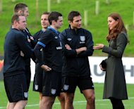 Catherine the Duchess of Cambridge (R) speaks with England footballers Adam Johnson (3rd R) and Frank Lampard (2nd R) as teammates Wayne Rooney (L), Gary Cahill (2nd L) and Phil Jagielka look on during the official opening of The Football Association's National Football Centre at St George's Park in Burton-upon-Trent, England
