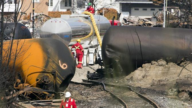 """FILE - This July 6, 2013 file-pool photo shows work continuing at the crash site of the train derailment and fire in Lac-Megantic, Quebec. Federal inspection teams are headed to the booming Bakken oil region in Great Plains states to see if rail shipments of crude oil meet safety regulations. The inspections are dubbed the """"Bakken blitz."""" U.S. officials announced them at a rail safety meeting Thursday. Inspections were prompted by last month's rail disaster in the lakeside Quebec town of Lac-Megantic, near the Maine border. An unattended train carrying oil from the Bakken region came loose and derailed, sending tank cars into the center of the town, where they exploded. Forty-seven people were killed and much of the town was destroyed. (AP Photo/Ryan Remiorz, Pool)"""