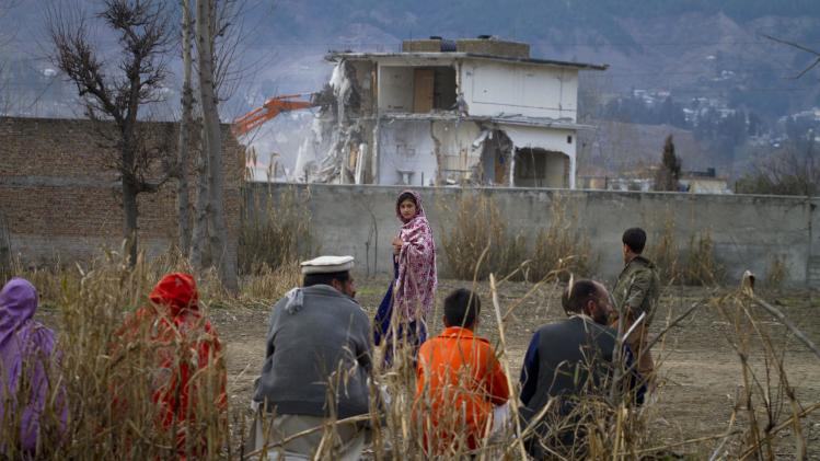 FILE - In this Feb. 26, 2012 file picture, a Pakistan family watches the destruction of Osama bin Laden's compound in Abbottabad, Pakistan. Bin Laden spent his last weeks in a house divided, amid wives riven by suspicions. On the top floor, sharing his bedroom, was his youngest wife and favorite. The trouble came when his eldest wife showed up and moved into the bedroom on the floor below. (AP Photo/Anjum Naveed, File)