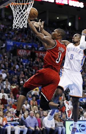 Miami Heat center Chris Bosh (1) shoots in front of Oklahoma City Thunder forward Serge Ibaka (9) in the first quarter of an NBA basketball game in Oklahoma City, Thursday, Feb. 14, 2013. (AP Photo/Sue Ogrocki)