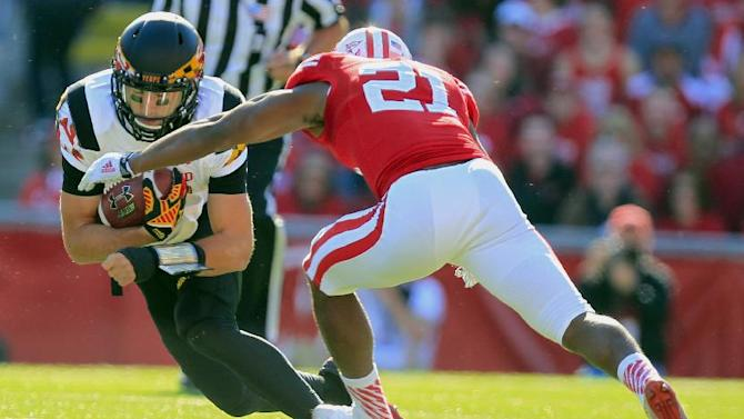 Wisconsin cornerback Peniel Jean (21) tackles Maryland quarterback C.J. Brown (16) during the first half of an NCAA college football game Saturday, Oct. 25, 2014, in Madison, Wis