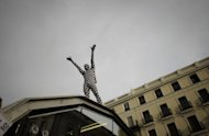 A Spanish &quot;indignant&quot; protester stands on top of a subway station entrance during a demonstration at the Puerta del Sol square in Madrid