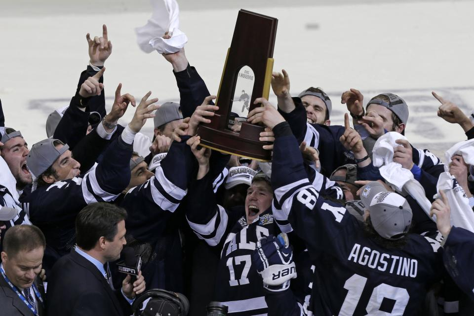 Yale captain Andrew Miller (17) hoists the trophy for winning the NCAA men's college hockey Frozen Four national championship game over Quinnipiac 4-0, in Pittsburgh, Saturday, April 13, 2013.  (AP Photo/Gene Puskar)