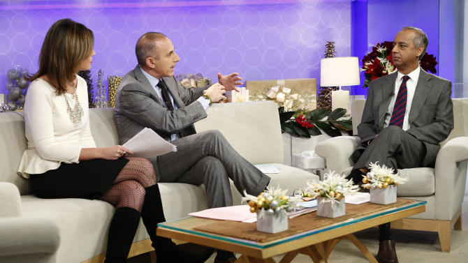 """This image released by NBC shows co-hosts Savannah Guthrie, left, and Matt Lauer, center, during an interview with freelance photographer R. Umar Abbasi on NBC News' """"Today"""" show, Wednesday, Dec. 5, 2012 in New York. On Monday, Abbasi took a photo of a man who was pushed onto a New York subway track and killed after being hit by a train. The New York Post published the photo on its front page Tuesday showing the man with his head turned toward the oncoming train. The headline read in part: """"This man is about to die."""" (AP Photo/NBC, Peter Kramer)"""
