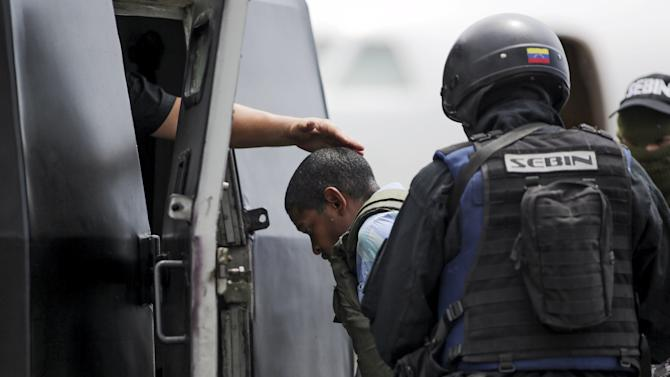 "Leiver Padilla Mendoza, alias ""El Colombia"", is escorted by police officers as he gets into a car, after being extradited from Colombia, at Simon Bolivar Airport in Caracas"