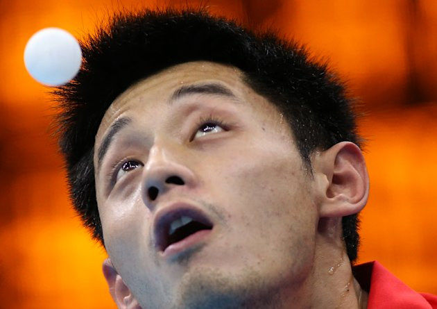 China's Zhang Jike eyes the ball during a match against Germany's Timo Boll in a men's team table tennis semifinal at the 2012 Summer Olympics, Monday, Aug. 6, 2012, in London. (AP Photo/Sergei Grits)