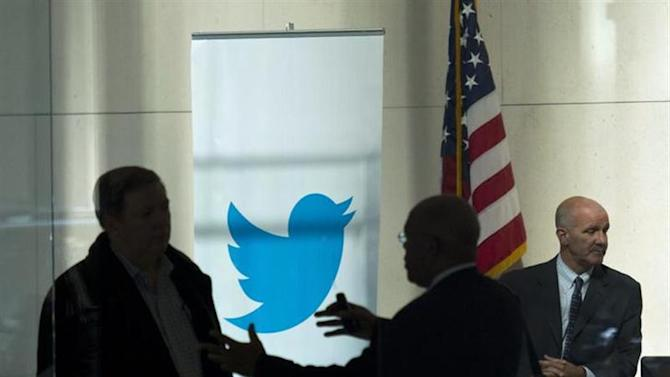 People talk inside JP Morgan headquarters near a Twitter banner, before the firm's IPO in New York, October 25, 2013. REUTERS/Eduardo Munoz