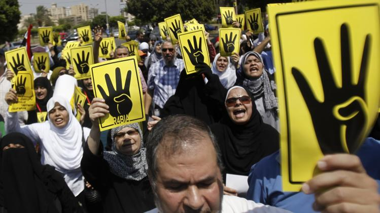 "Members of the Muslim Brotherhood and supporters of ousted Egyptian President Mursi make the ""Rabaa"" gesture during a protest in Cairo"