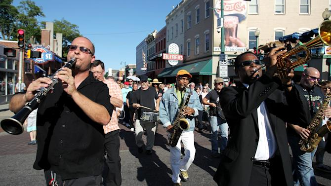 "Tom Link, from left, Kirk Whalum and Philip Joyner Jr. perform in a processional down Beale Street in Memphis, Tenn., Wednesday May 23, 2012,  to honor and celebrate Stax great Donald ""Duck"" Dunn. Dunn, best known as the bass player for Booker T. & the MG's that helped define the Stax sound, was laid to rest Wednesday after passing away May 13 while on tour in Tokyo at age 70. (AP Photo/The Commercial Appeal, Mike Brown)"