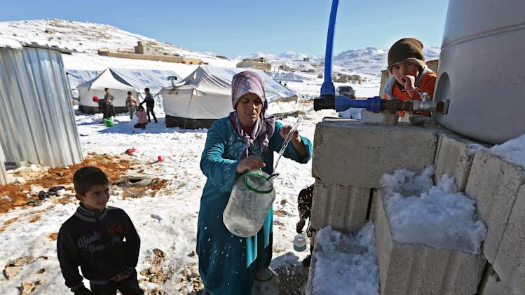 A Syrian refugee woman fetches water at a refugee camp in the eastern Lebanese border town of Arsal, Lebanon, Sunday, Dec. 15, 2013. Tens of thousands of impoverished Syrian refugees living in tents, shacks and unfinished buildings throughout Lebanon face a miserable winter as aid organizations scramble to meet their needs, constantly overwhelmed by ever-more Syrians fleeing their country's war. Charities have already distributed blankets, mattresses, kerosene heaters, winter clothes and coupons for fuel ahead of the region's unprecedented storm this week that blanketed parts of Lebanon, the Palestinian Territories, Turkey, Israel and even Egypt's deserts with snow, amid icy and rainy winds. (AP Photo/Bilal Hussein)