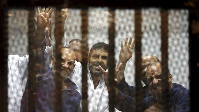 Muslim Brotherhood's senior member Mohamed El-Beltagy and deputy head of the Freedom and Justice Party Essam El-Erian wave Rabia sign, behind bars with other Muslim Brotherhood members at a court in the outskirts of Cairo