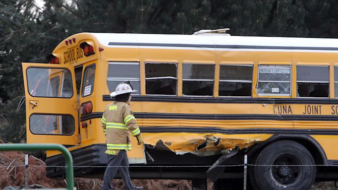 A firefighter walks past the damaged Kuna School District bus at the scene of a fatal crash on Thursday, Dec. 5, 2013 in Kuna, Idaho. Authorities say one child has died and five people were injured, including four children, when a dump truck collided with the school bus carrying elementary school students in Kuna, a town about 30 minutes from Boise. Canyon County Sheriff spokeswoman Theresa Baker confirmed the death and said the parents have been notified. Baker says as many as 10 children in the sixth grade or younger were on a bus destined for Crimson Point Elementary School. (AP Photo/The Idaho Statesman, Darin Oswald) LOCAL TV OUT, KTVB 7 OUT THE IDAHO PRESS-TRIBUNE OUT
