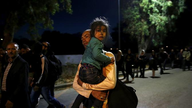 Afghan and Syrian refugees walk after been rescued by Greek coast guard on Kos