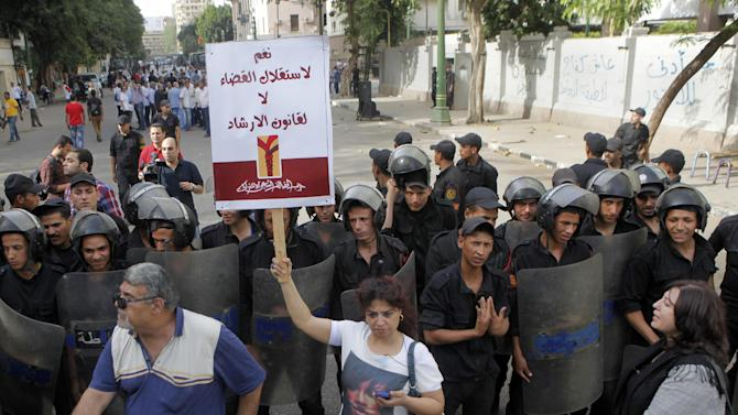 """An Egyptian opposition activist holds an Arabic poster which reads, """"Yes for judicial independence, no for Brotherhood law,"""" as  anti-riot soldiers prevent activists from reaching the Shura Council, the upper house of Parliament, during a protest against the new judicial law in Cairo, Egypt, Saturday, May 25, 2013.  (AP Photo/ Amr Nabil)"""