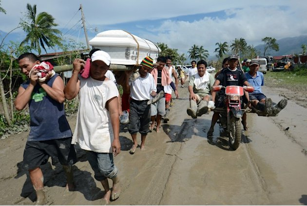 Residents carry the coffin of a dead relative in New Bataan town, compostela province on December 6, 2012.