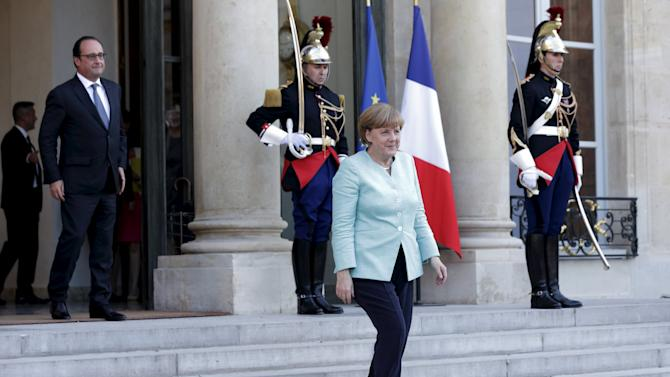 French President Hollande looks at German Chancellor Merkel as she leaves the Elysee Palace in Paris