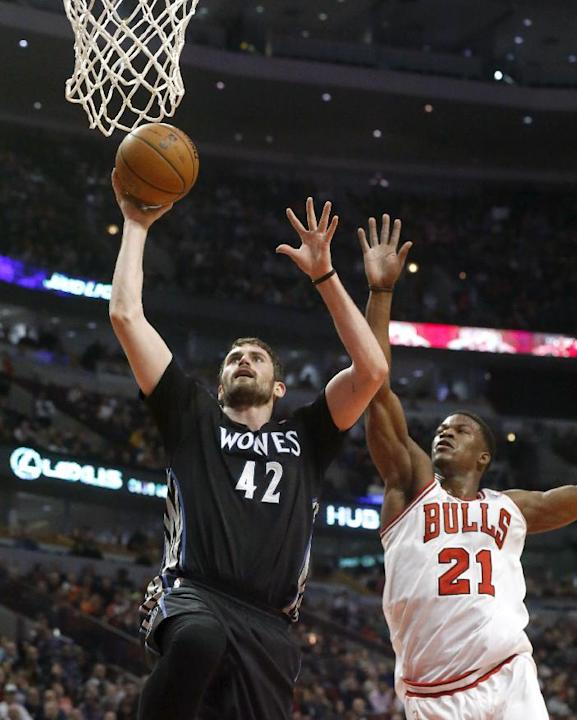 Minnesota Timberwolves forward Kevin Love (42) scores past Chicago Bulls guard Jimmy Butler (21) during the first half of an NBA basketball game, Monday, Jan. 27, 2014, in Chicago