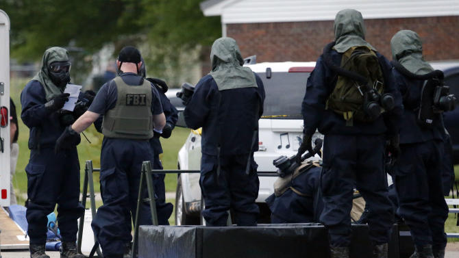 Armed federal agents wearing hazardous material suits and breathing apparatus begin personal cleanup after entering the West Hills Subdivision home of Paul Kevin Curtis in Corinth, Miss., Thursday evening April 18, 2013. All suits and gear, including weapons were placed in hazardous materials bags for extensive cleanup. Law enforcement officials blocked off the dwelling after taking Curtis into custody under the suspicion of sending letters covered in ricin to the U.S. President Barack Obama and U.S. Sen. Roger Wicker, R-Miss. (AP Photo/Rogelio V. Solis)