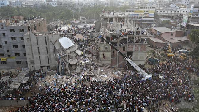 Bangladeshis watch the rescue operations at the site of a building that collapsed Wednesday in Savar, near Dhaka, Bangladesh, Thursday, April 25, 2013. By Thursday, the death toll reached at least 194 people as rescuers continued to search for injured and missing, after a huge section of an eight-story building that housed several garment factories splintered into a pile of concrete. (AP Photo/Kevin Frayer)