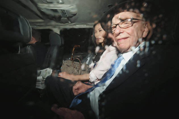 News Corp. chairman Rupert Murdoch, right, and his wife Wendi Deng sit in the back of a car as they are driven to the Leveson inquiry at the High Court in London, Thursday, April 26, 2012.  (AP Photo/