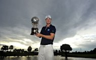 This handout photograph released and taken by the World Sport Group shows Chris Wood of England with the winner's trophy during the final day of the Thailand Open at the Suwan golf and country club on the outskirts of Bangkok