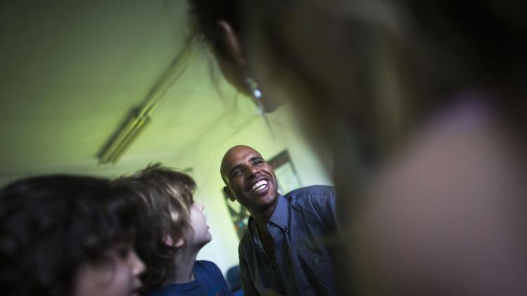 Angesom Solomon, a 28-year-old African migrant from Eritrea, smiles during a Hebrew lesson at a school in Tel Aviv