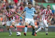 Stoke City's Michael Owen (L) clashes for the ball with Manchester City's Javi Garcia (C) during the Premiership football match at The Brittania Stadium in Stoke. The game ended 1-1