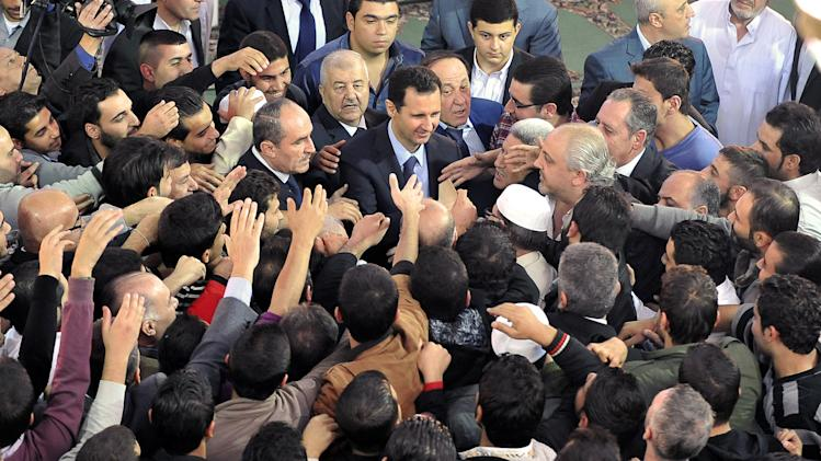In this photo released by the Syrian official news agency SANA, Syrian President Bashar Assad, center, greets his supporters after he attended prayers on the first day of Eid al-Adha, at the Sayeda Hassiba mosque, in Damascus, Syria, Tuesday, Oct. 15, 2013. (AP Photo/SANA)
