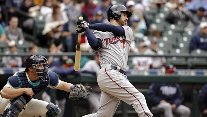 Minnesota Twins' Joe Mauer, right, hits a triple to drive in a pair of runs as Seattle Mariners catcher Mike Zunino looks on in the 11th inning of a baseball game Sunday, April 26, 2015, in Seattle. (AP Photo/Elaine Thompson)