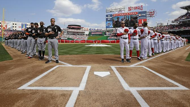 The Washington Nationals and Miami Marlins stand for a moment of silence honoring the victims of the Sandy Hook Elementary School shooting before the opening day baseball game in Washington, on Monday, April 1, 2013.  (AP Photo/Alex Brandon)