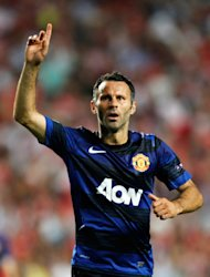 Manchester United's Ryan Giggs, raises his hand celebrating after scoring against Benfica during their Champions League group C soccer match at Benfica's Luz stadium in Lisbon. Wednesday, Sept. 14 2011. (AP Photo/Armando Franca)