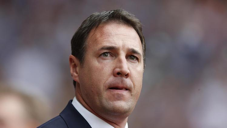 FILE - This is a Saturday, Aug. 17, 2013 file photo of the then Cardiff City's manager Malky Mackay as he looks on from the dugout before the start of their English Premier League soccer match against West Ham United at Upton Park, London. The English Football Association siad Thursday Aug. 21, 2014 that it has opened an investigation after Cardiff submitted a dossier to the governing body about the conduct of former manager Malky Mackay and a member of his backroom staff. (AP Photo/Sang Tan/ File)