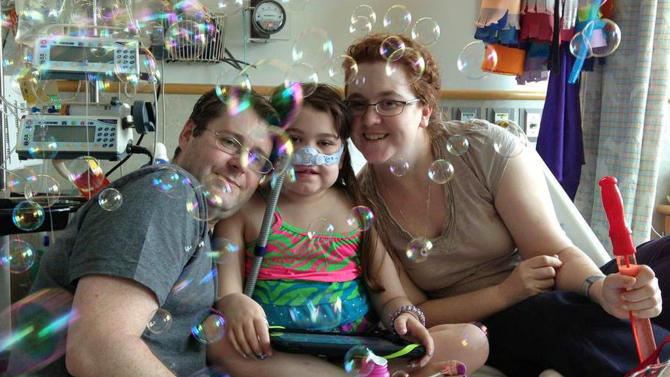 FILE - In this May 30, 2013 file photo provided by the Murnaghan family, Sarah Murnaghan, center, celebrates the 100th day of her stay in Children's Hospital of Philadelphia with her father, Fran, left, and mother, Janet. A federal judge in Philadelphia on Wednesday, June 5, 2013 made the dying 10-year-old eligible to seek donor lungs from an adult transplant list. Who gets the next donated organ is a life or death matter, and now a judge is allowing two dying children in Pennsylvania to essentially jump the line. It's an unprecedented challenge to the nation's transplant system that specialists say raises serious questions of fairness. (AP Photo/Murnaghan Family, File)