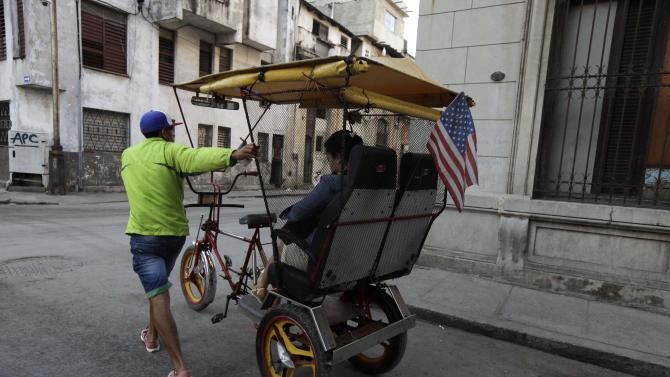 Man pushes his tricycle taxi with a U.S flag on a street in Havana