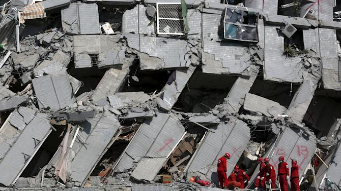 Rescue personnel work at the site where a 17-storey apartment building collapsed after an earthquake hit Tainan