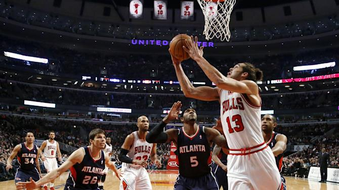Chicago Bulls center Joakim Noah (13) shoots a reverse layup past Atlanta Hawks' Kyle Korver (26) and Josh Smith (5) during the first half of an NBA basketball game Monday, Jan. 14, 2013, in Chicago. (AP Photo/Charles Rex Arbogast)