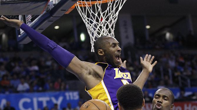 Los Angeles Lakers guard Kobe Bryant (24) loses control of the ball between Oklahoma City Thunder guard Thabo Sefolosha (2)  and forward Serge Ibaka, right, in the second quarter of an NBA basketball game in Oklahoma City, Friday, Dec. 7, 2012. (AP Photo/Sue Ogrocki)