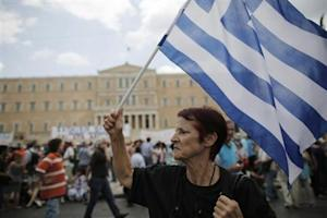 An anti-austerity protester holds a Greek flag during a rally in Athens